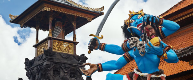 Blue coloured traditional demon ogoh-ogoh holding a severed head and decorated with skulls before the annual parade of horrible monsters - pengrupukan, which is held in the evening of Nyepi - Balinese New Year before the day of silence